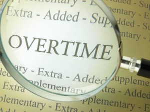 "The word ""overtime"" seen through a magnifying glass"